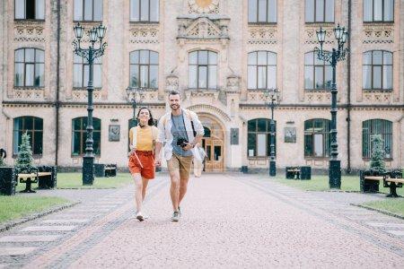 Photo pour Heureux coupé tenant la main tout en marchant près du campus universitaire - image libre de droit