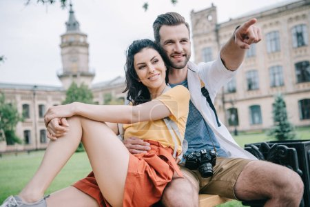 happy man pointing with finger while sitting with beautiful girl