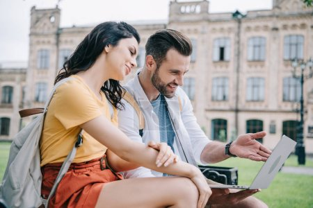 Photo for Attractive young woman sitting near bearded man using laptop - Royalty Free Image