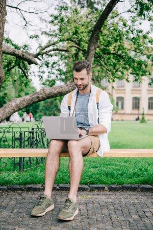 Photo pour Beau blogueur barbu tapant sur ordinateur portable près de l'université - image libre de droit