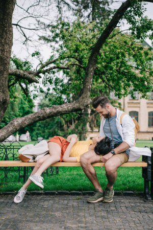 Photo for Happy man looking at girl lying on bench near building - Royalty Free Image
