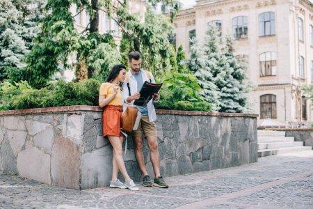 Photo pour Homme barbu et femme attirant restant près du bâtiment avec l'atlas - image libre de droit