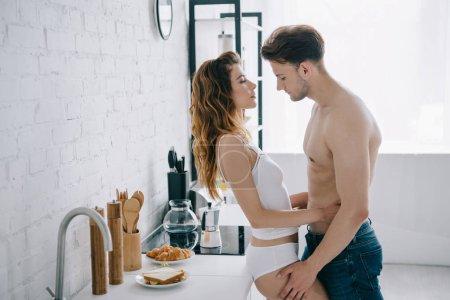 Photo pour Vue latérale de la petite amie attrayante et beau petit ami étreignant dans l'appartement - image libre de droit