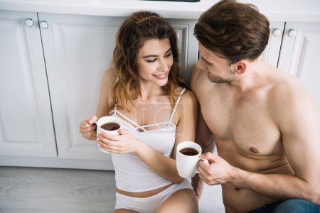 Photo for High angle view of attractive girlfriend and handsome boyfriend smiling and holding cups in apartment - Royalty Free Image