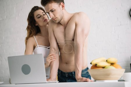Photo for Attractive woman hugging and handsome boyfriend using laptop in apartment - Royalty Free Image