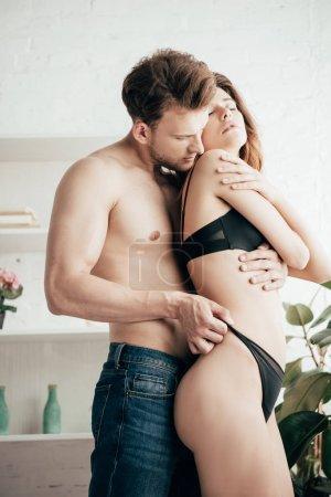 Photo for Handsome boyfriend hugging attractive girlfriend in black underwear - Royalty Free Image