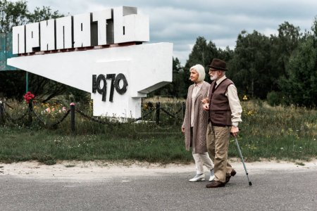 Photo for PRIPYAT, UKRAINE - AUGUST 15, 2019: retired man and woman walking near monument with pripyat letters - Royalty Free Image