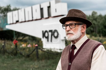Photo for PRIPYAT, UKRAINE - AUGUST 15, 2019: senior bearded man in glasses standing near monument with pripyat letters - Royalty Free Image