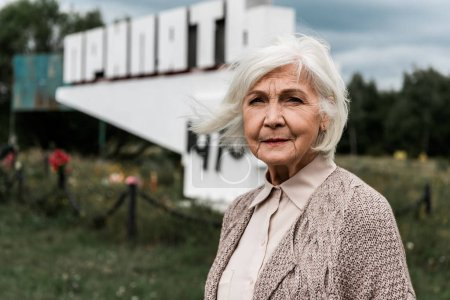 Photo for PRIPYAT, UKRAINE - AUGUST 15, 2019: senior woman standing near monument with pripyat letters - Royalty Free Image