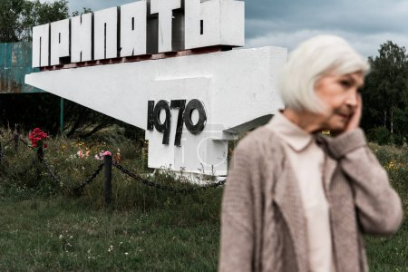 Photo for PRIPYAT, UKRAINE - AUGUST 15, 2019: retired woman standing near monument with pripyat letters - Royalty Free Image