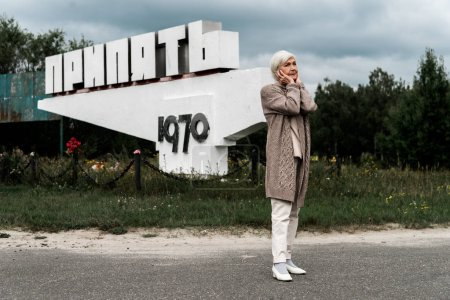 Photo for PRIPYAT, UKRAINE - AUGUST 15, 2019: retired woman standing near monument with pripyat letters and covering ears - Royalty Free Image