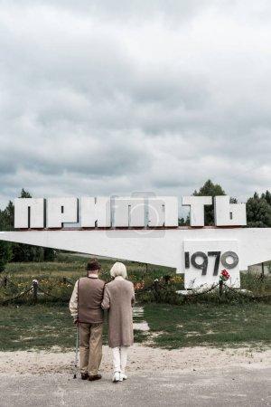 Photo pour Pripyat, Ukraine - 15 août 2019: vue arrière de mari et femme à la retraite debout près du monument avec des lettres pripyat - image libre de droit