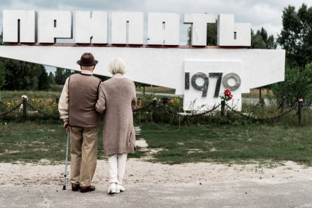 Photo for PRIPYAT, UKRAINE - AUGUST 15, 2019: back view of retired couple standing near monument with pripyat letters - Royalty Free Image