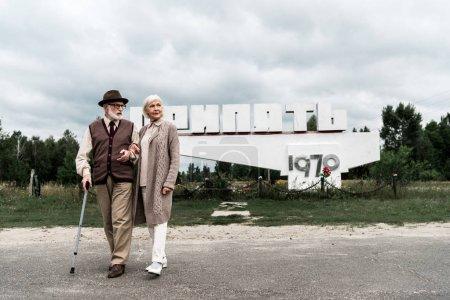 Photo pour Pripyat, Ukraine - 15 août 2019: couple aîné marchant près du monument avec des lettres de pripyat - image libre de droit
