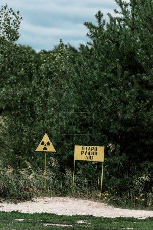 PRIPYAT, UKRAINE - AUGUST 15, 2019: chernobyl zone with yellow warning signs near green trees