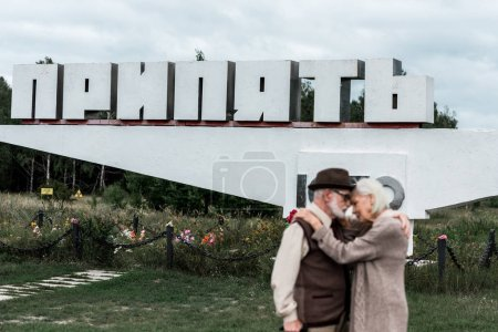 Photo for PRIPYAT, UKRAINE - AUGUST 15, 2019: selective focus of monument with pripyat letters near senior couple hugging outside - Royalty Free Image