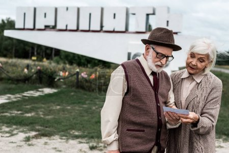 Photo for PRIPYAT, UKRAINE - AUGUST 15, 2019: retired couple looking at photo near monument with pripyat letters - Royalty Free Image