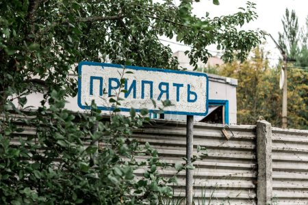 Photo for PRIPYAT, UKRAINE - AUGUST 15, 2019: sign with pripyat lettering near trees and fence - Royalty Free Image
