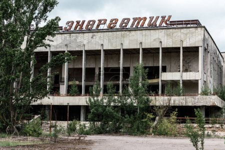 Photo for PRIPYAT, UKRAINE - AUGUST 15, 2019: building with energetic lettering near green trees in chernobyl - Royalty Free Image