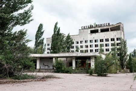 Photo for PRIPYAT, UKRAINE - AUGUST 15, 2019: building with hotel polissya lettering near trees in chernobyl - Royalty Free Image