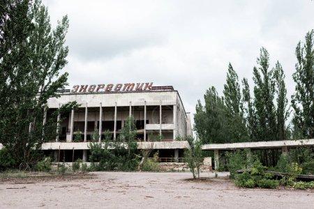 pripjat, Ukraine - 15. August 2019: Gebäude mit energetischen Buchstaben in der Nähe grüner Bäume in Tschernobyl