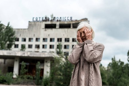 Photo for PRIPYAT, UKRAINE - AUGUST 15, 2019: senior woman covering face near building with hotel polissya lettering in chernobyl - Royalty Free Image