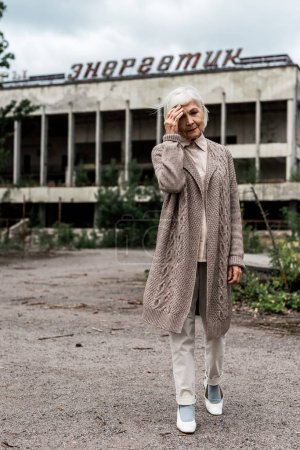 Photo for PRIPYAT, UKRAINE - AUGUST 15, 2019: senior woman walking near building with energetic lettering in chernobyl - Royalty Free Image