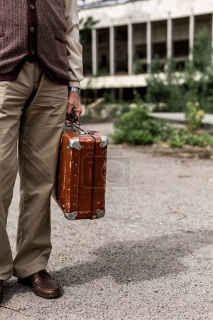 Photo for Cropped view of senior man holding travel bag - Royalty Free Image