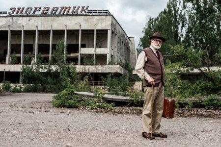 Photo pour Pripyat, Ukraine - 15 août 2019: homme aîné dans les bagages de fixation de chapeau près du bâtiment avec le lettrage énergique dans tchernobyl - image libre de droit