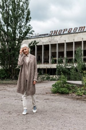 PRIPYAT, UKRAINE - AUGUST 15, 2019: senior woman walking near building with energetic lettering in chernobyl
