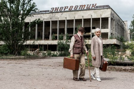 Photo for PRIPYAT, UKRAINE - AUGUST 15, 2019: retired travelers with suitcases near building with energetic lettering in chernobyl - Royalty Free Image