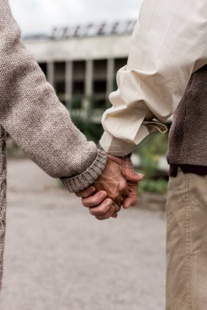 Photo for Cropped view of retired husband and wife holding hands - Royalty Free Image