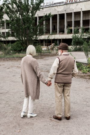 Photo for PRIPYAT, UKRAINE - AUGUST 15, 2019: back view of retired man and woman holding hands near building - Royalty Free Image