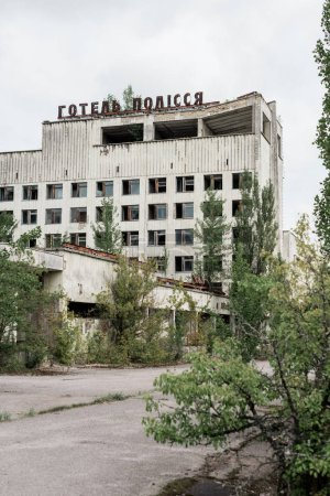 Photo pour Pripyat, Ukraine - 15 août 2019: bâtiment avec des lettres polissya hôtel près des arbres à Tchernobyl - image libre de droit