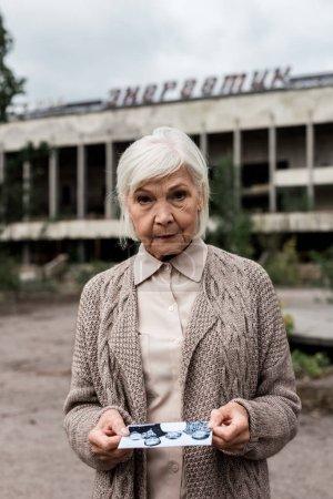 Photo pour Pripyat, Ukraine - 15 août 2019: femme âgée tenant la photo près du bâtiment avec le lettrage énergique dans tchernobyl - image libre de droit