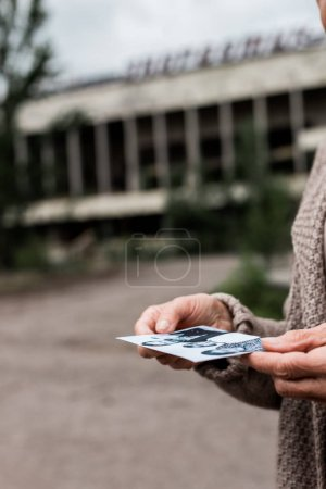Photo for PRIPYAT, UKRAINE - AUGUST 15, 2019: cropped view of senior woman holding black and white photo near building - Royalty Free Image