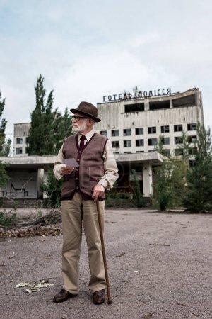 Photo pour Pripyat, Ukraine - 15 août 2019: homme aîné avec la canne de marche tenant la photo près du bâtiment avec des lettres d'hôtel polissya - image libre de droit