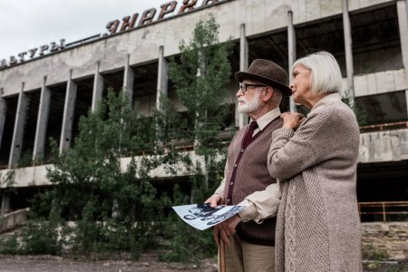 Photo for PRIPYAT, UKRAINE - AUGUST 15, 2019: retired man and woman holding black and white photo near building with lettering in chernobyl - Royalty Free Image