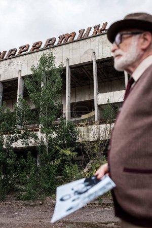 Photo pour Pripyat, Ukraine - 15 août 2019: focus sélectif de la construction avec lettrage homme aîné tenant la photo - image libre de droit