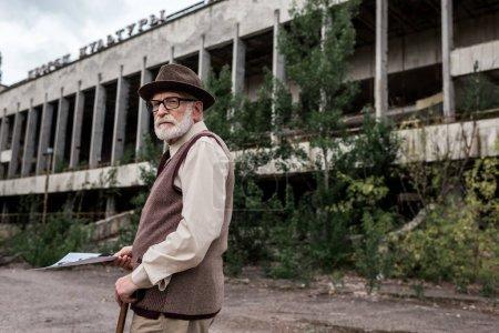 Photo pour Pripyat, Ukraine - 15 août 2019: un homme âgé tenant une photo près d'un bâtiment à Tchernobyl - image libre de droit