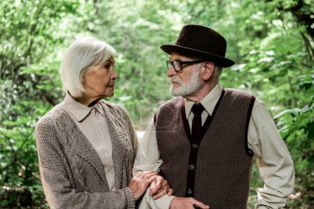 Photo for Senior man in glasses looking at woman near green trees - Royalty Free Image