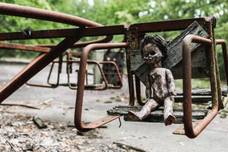 Photo for Burnt baby doll on abandoned carousel in chernobyl - Royalty Free Image