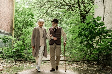 Photo for Retired woman and senior man with walking cane walking near green trees - Royalty Free Image