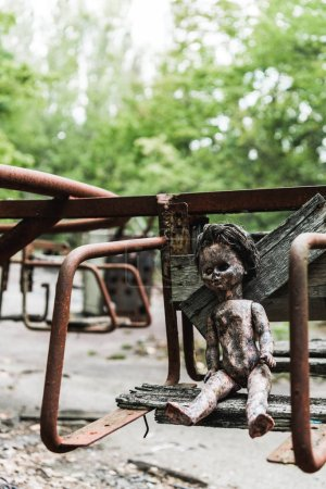 Photo for Selective focus of dirty baby doll on abandoned carousel in chernobyl - Royalty Free Image