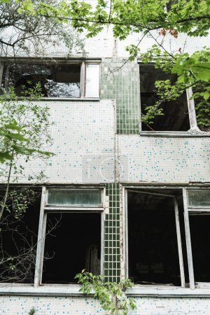 Photo for Selective focus of abandoned building near green trees in chernobyl - Royalty Free Image