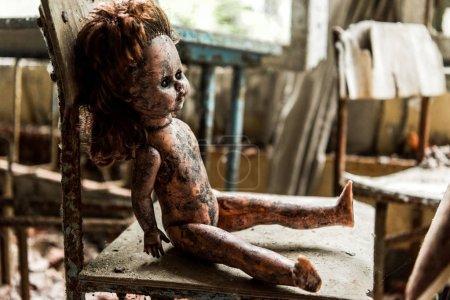 Photo pour Foyer sélectif de poupée de bébé sale et brûlé sur chaise en bois à l'école - image libre de droit