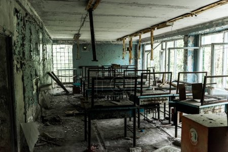 Photo for Abandoned and creepy classroom with dirty tables in school - Royalty Free Image