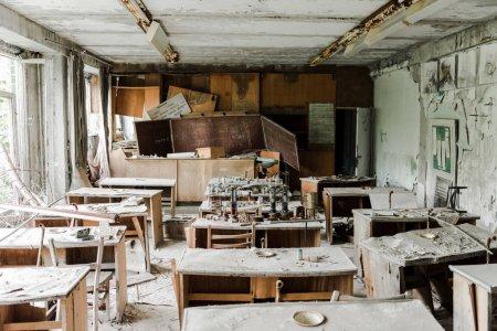 Foto de Aula abandonada y espeluznante con mesas sucias y tabla de tiza en la escuela - Imagen libre de derechos