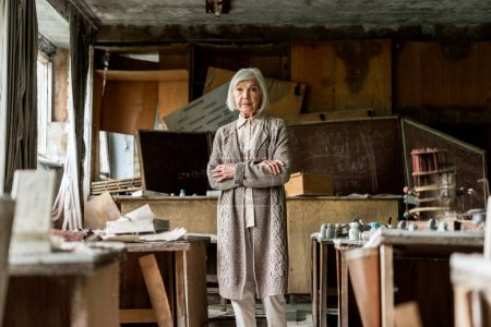 selective focus of retired woman standing with crossed arms near dirty tables