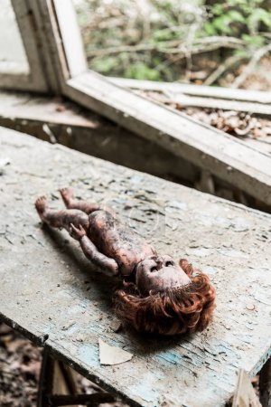 Photo for Selective focus of creepy burnt baby doll on wooden damaged desk - Royalty Free Image